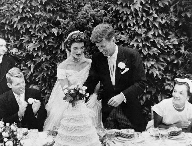 12 Sep 1953, Newport, Aquidneck Island, Rhode Island, USA --- Original caption: John F. Kennedy and Jacqueline Bouvier cutting their wedding cake after their marriage in Newport, Rhode Island. John Kennedy was then U.S. Senator from Massachusetts. Robert Kennedy at left. --- Image by © Bettmann/CORBIS